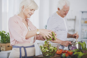 Older woman tossing a salad and her husband stirring food in a pot, cooking healthy together