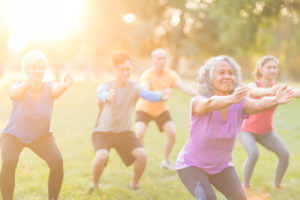 A multiethnic, coed group of various ages works out together outside in the early morning as the sun rises. They are doing a stretching exercise with their arms extended out in front of them.