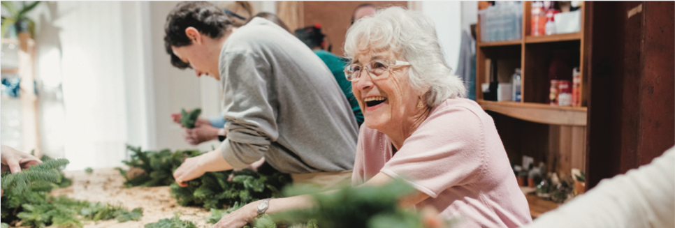 Photo focused on senior woman smiling while putting together a wreath